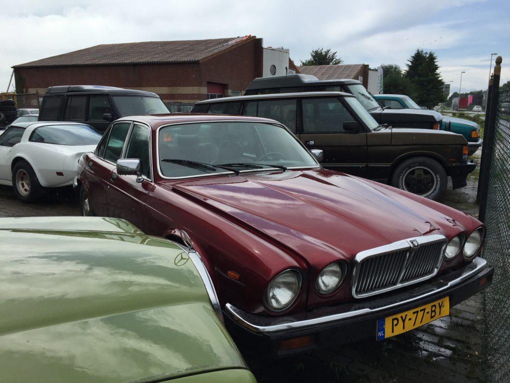 Dunkelroter XJ Serie III, dreiseitig eingekeilt von einem Mercedes W123, einer weißen Corvette C3 und zwei Range Rover der ersten Generation
